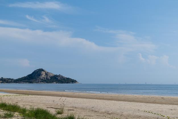 Spokojna plaża z niebieskim niebem w dnia świetle.