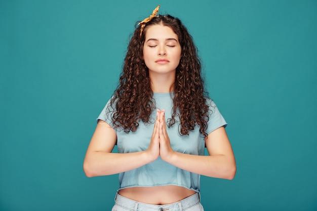 Spokojna, pogodna dziewczyna z kręconymi włosami trzymająca się za ręce w namaste podczas medytacji z zamkniętymi oczami na niebiesko