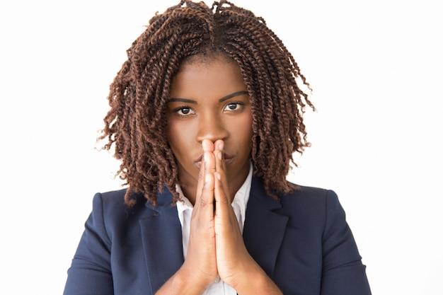 Spokojna poważna kobieta robi modlić się gestowi