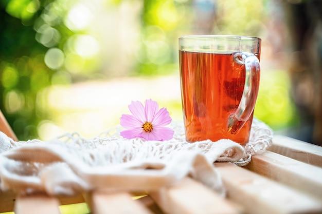Spokojna przyjemna martwa natura w ogrodzie z kubkiem herbaty i kwiatami w lecie