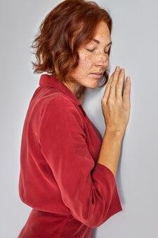Spokojna ruda kobieta w sukience oparta o ścianę z zamkniętymi oczami, portret instudio