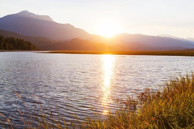 Spokojna scena nad górskim jeziorem w kanadzie z odbiciem skał w spokojnej wodzie.