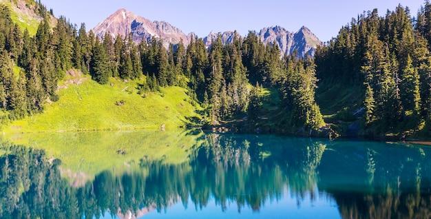 Spokojna scena nad górskim jeziorem z odbiciem skał w spokojnej wodzie.