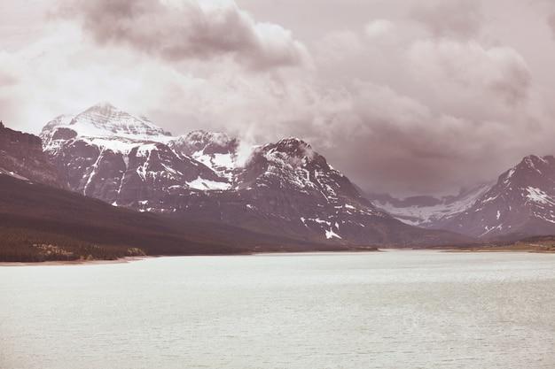 Spokojna scena nad jeziorem górskim w kanadzie z odbiciem skał w spokojnej wodzie.