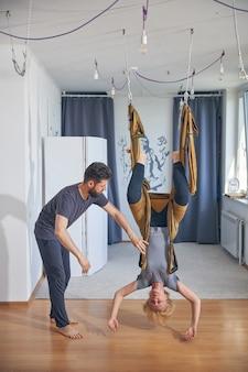 Spokojna, silna blondynka dojrzała joginka wykonująca ćwiczenie antygrawitacyjne w asyście wykwalifikowanego trenera