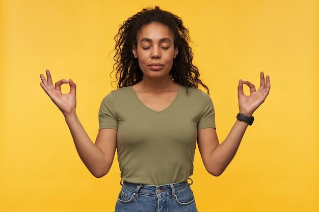 Spokojna, spacyfikowana młoda kobieta w zwykłych ubraniach trzyma oczy zamknięte i ręce w pozycji mudra stojąc i medytując na białym tle nad żółtą ścianą
