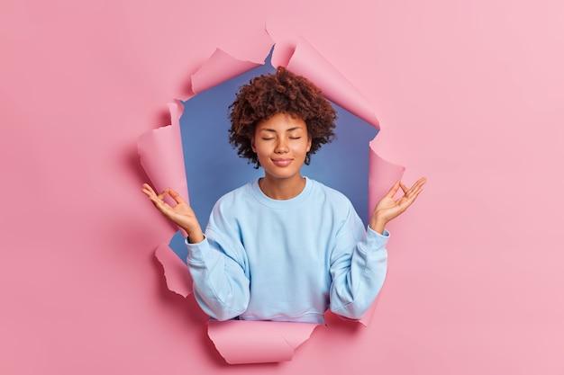 Spokojna, spokojna, ciemnoskóra młoda kobieta pokazuje gest w porządku lub zen medytuje w pomieszczeniu z zamkniętymi oczami