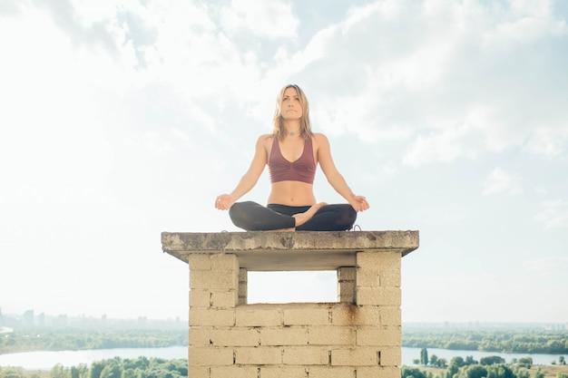 Spokojna spokojna dziewczyna siedzi w pozycji lotosu na dachu