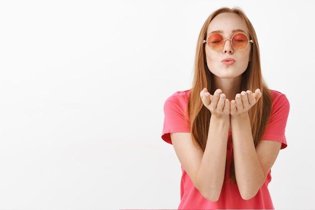 Spokojna, spokojna i delikatna europejska ruda dziewczyna z piegami zamykającymi oczy, składanymi ustami i dmuchającym pocałunkiem wyrażającym miłość, pasję i romans
