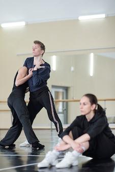 Spokojna spokojna kobieta w czarnym stroju siedzi na podłodze w studio tańca, podczas gdy młoda para tańczy w pobliżu
