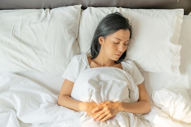 Spokojna, spokojna młoda dama ma na sobie piżamę, która śpi na łóżku. widok z góry