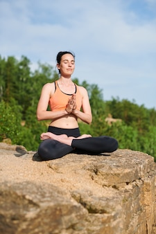Spokojna, spokojna młoda dama siedzi w pozycji lotosu na kamieniu w górach podczas medytacji na świeżym powietrzu