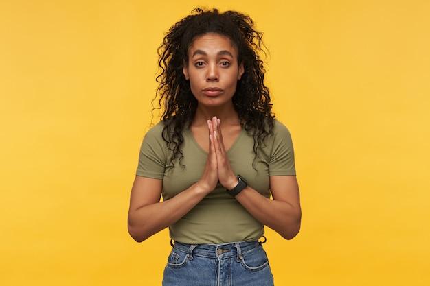 Spokojna, spokojna młoda kobieta w zwykłych ubraniach stoi i trzyma ręce w pozycji modlącej się odizolowanej nad żółtą ścianą