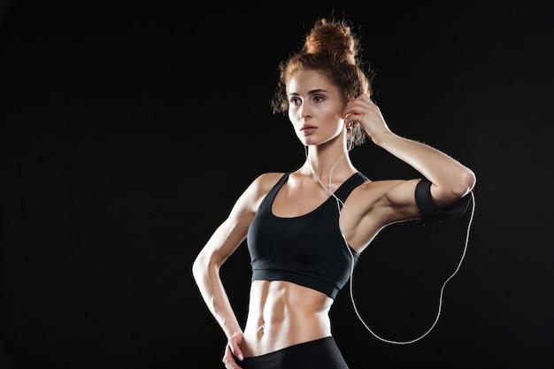 Spokojna sprawności fizycznej kobieta pozuje muzykę i słucha