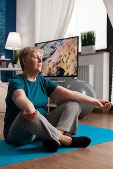 Spokojna starsza kobieta siedzi wygodnie w pozycji lotosu na macie do jogi z zamkniętymi oczami