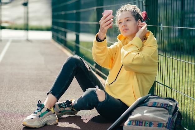 Spokojna stylowa studentka przyglądająca się uważnie swojemu odbiciu w lustrze na boisku sportowym