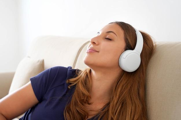 Spokojna tysiącletnia dziewczyna leży na wygodnej kanapie w bezprzewodowych słuchawkach i cieszy się dobrą medytacyjną muzyką. spokojna młoda kobieta w słuchawkach zrelaksować się słuchać audiobooka z zamkniętymi oczami.