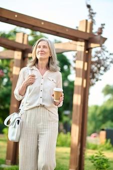 Spokojna uśmiechnięta kobieta z kawą na spacerze w parku