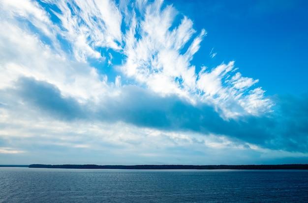 Spokojna woda i piękne błękitne niebo z chmurami na najbliższym brzegu rosną drzewa