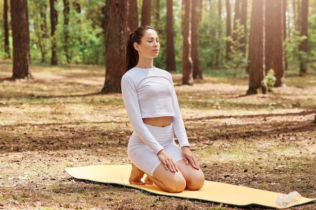 Spokojna wysportowana kobieta ciesząca się świeżym powietrzem podczas treningu w lesie, z zamkniętymi oczami, siedząca na macie gimnastycznej ćwiczącej jogę, medytująca