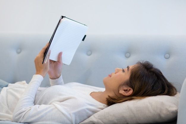 Spokojna zrelaksowana dziewczyna leżąc na plecach i czytając książkę