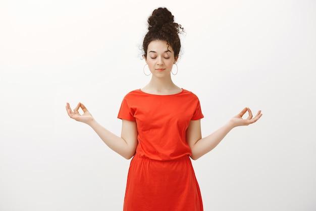 Spokojna zrelaksowana kobieca kobieta z kręconymi włosami zaczesanymi w kok