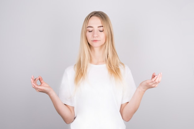 Spokojna, zrelaksowana ładna blondynka łagodzi stres, zamyka oczy i uśmiecha się spokojnie, medytując