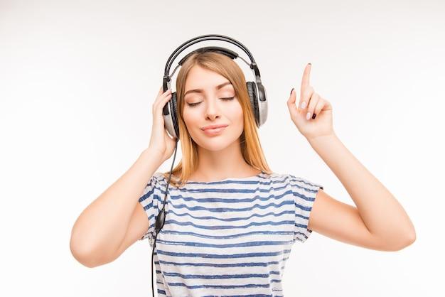 Spokojna zrelaksowana młoda kobieta ze słuchawkami i zamkniętymi oczami