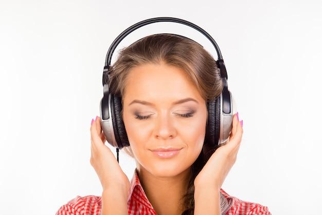 Spokojna zrelaksowana młoda kobieta ze słuchawkami