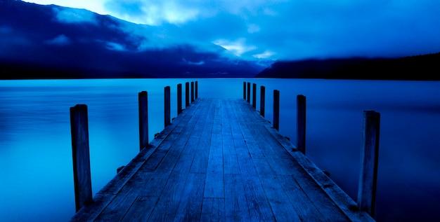 Spokojne jezioro z pomostem, nelson lakes, nowa zelandia wyspa południowa.