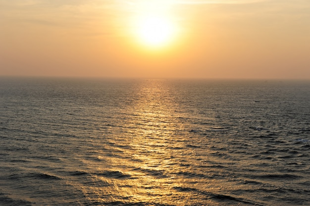 Spokojne morze w tajemniczym świetle zachodzącego słońca, mgła nad horyzontem.