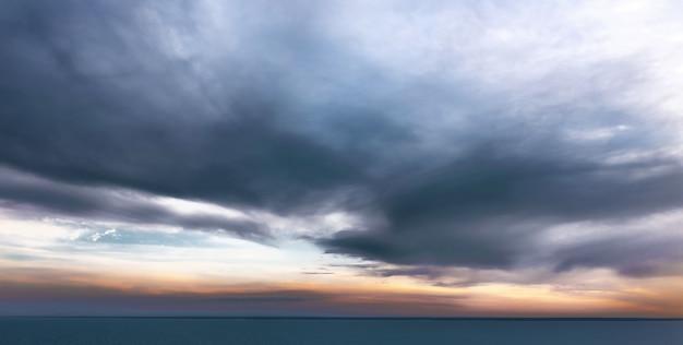 Spokojne morze z dramatycznym niebem z chmurami. spokojny krajobraz zachodu słońca