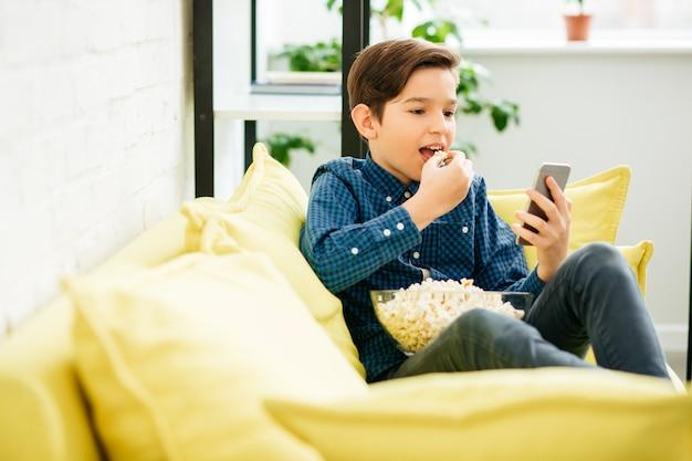 Spokojni uczniowie siedzący wygodnie na sofie i przyglądający się uważnie ekranowi smartfona w dłoni, jedząc popcorn