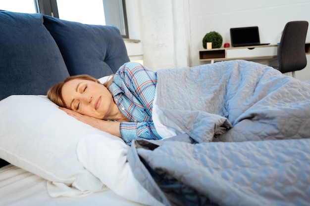 Spokojnie kłamie. spokojna kobieta w średnim wieku śpi samotnie w swoim łóżku, przykryta niebieskim kocem