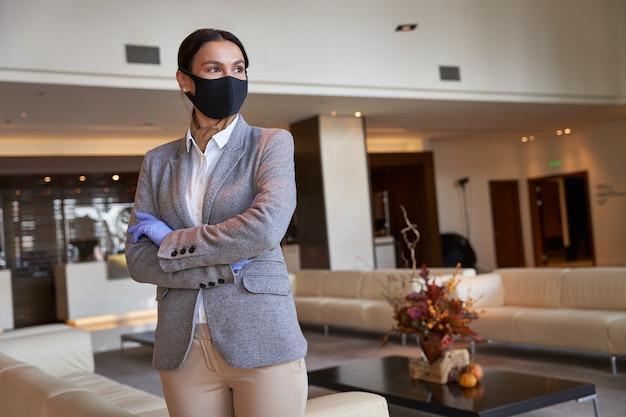 Spokojny administrator w masce z tkaniny i gumowych rękawiczkach stoi ze skrzyżowanymi rękami i odwraca wzrok. baner szablonu