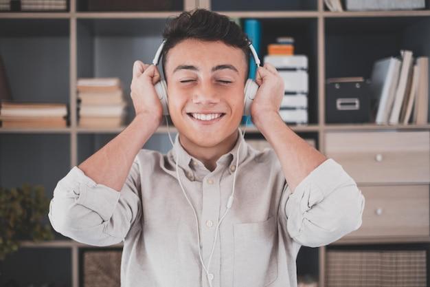 Spokojny beztroski młody nastolatek mężczyzna w domu, noszący nowoczesne bezprzewodowe słuchawki, słuchający ulubionej muzyki klasycznej online, czujący się spokojny, uważny sam w salonie.