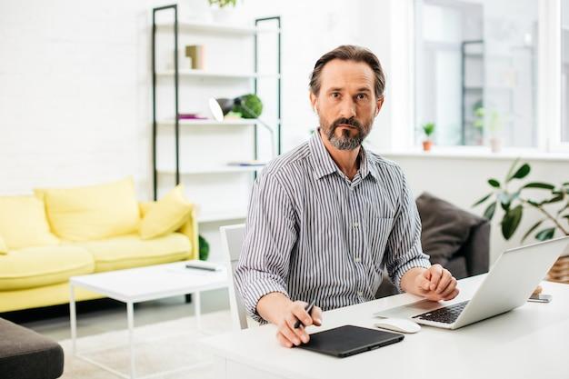 Spokojny brodaty mężczyzna w średnim wieku wyglądający poważnie, siedząc przy białym stole w salonie i mając u boku nowoczesny tablet graficzny