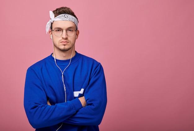 Spokojny chłopak w białej chustce i niebieskim swetrze słuchania muzyki przez słuchawki