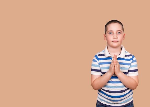 Spokojny chłopiec modlący się do boga z rękami złożonymi