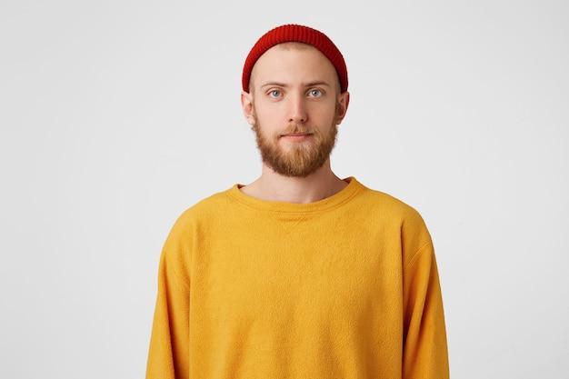 Spokojny ciekawy brodaty facet w czerwonym kapeluszu z normalnym wyrazem twarzy