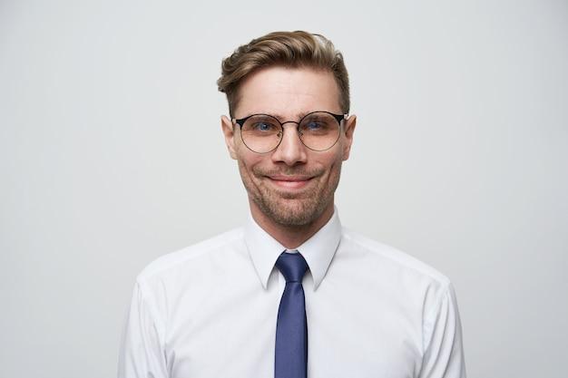 Spokojny, ciekawy nieogolony facet w białej koszuli i niebieskim krawacie z uśmiechem na twarzy
