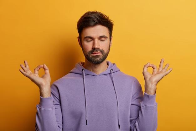 Spokojny, cierpliwy, brodaty mężczyzna unosi ręce na boki gestem zen, ma zamknięte oczy, odpoczywa po pracy lub nauce, jest cierpliwy, pozuje na żółtej ścianie, oddycha głęboko i odczuwa ulgę