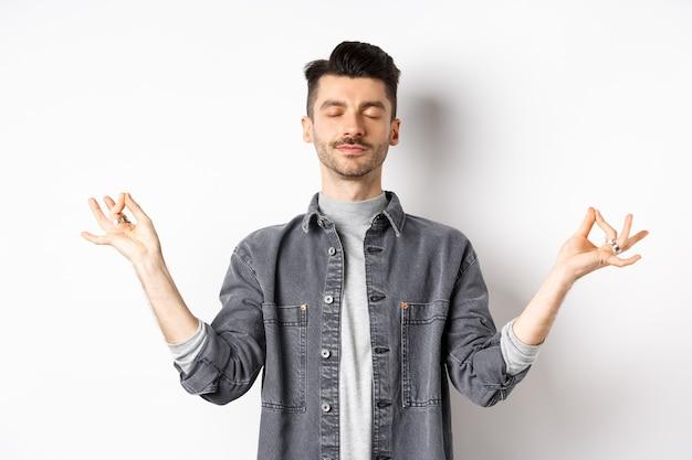 Spokojny facet medytujący ze spokojną twarzą, trzymając się za ręce w znaku zen mudra i zamykając oczy, ćwicz jogę, relaksując się na białym tle.