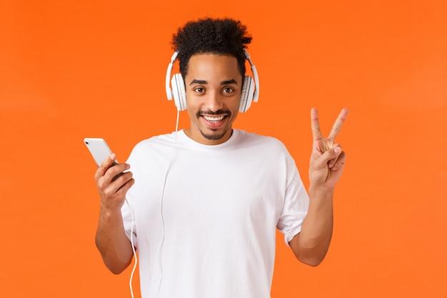 Spokojny i przyjazny, szczęśliwy afroamerykanin w białej koszulce, słuchaj muzyki w słuchawkach