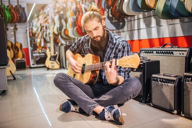 Spokojny i skoncentrowany młody człowiek siedzi na podłodze ze skrzyżowanymi nogami. gra na gitarze akustycznej. wiele gitar elektrycznych i głośników znajduje się w pokoju. facet siedzi sam.