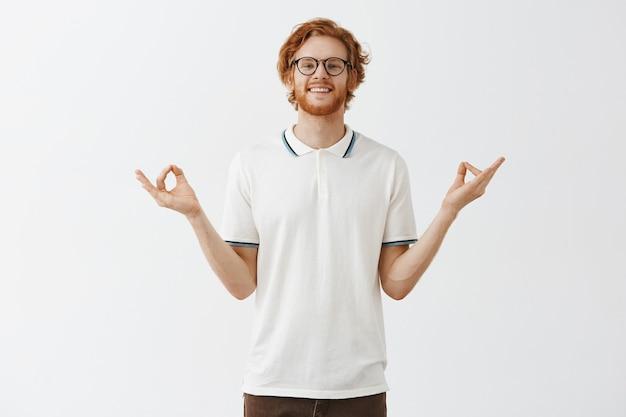 Spokojny i zrelaksowany brodaty rudy facet pozuje w okularach przy białej ścianie
