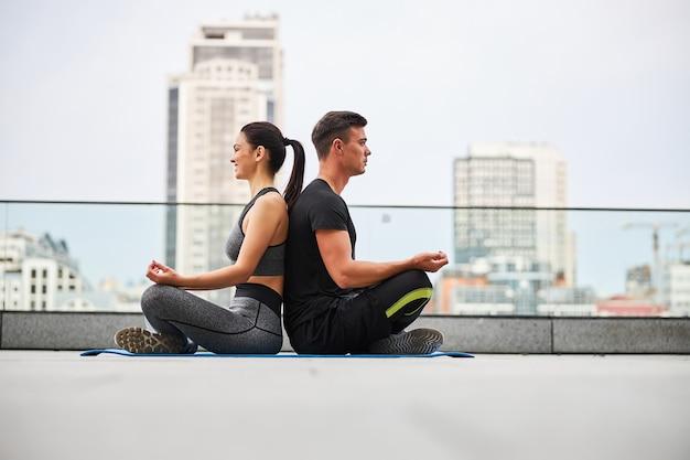 Spokojny mężczyzna i kobieta siedzą w pozycji lotosu, ćwicząc na szczycie w centrum miasta