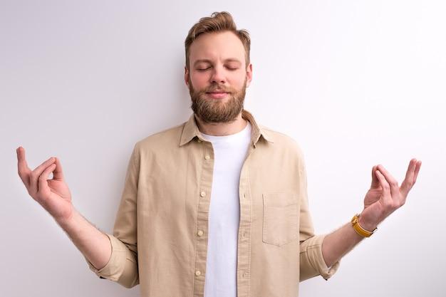 Spokojny mężczyzna medytujący w jodze, stojąc z zamkniętymi oczami. na białym tle białe studio, portret