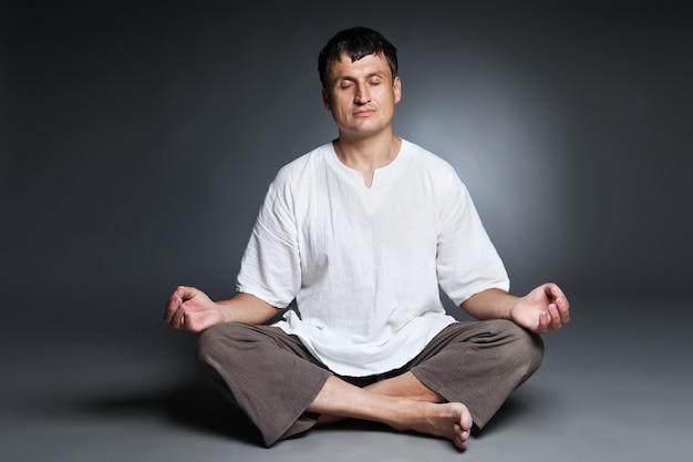 Spokojny mężczyzna uprawiający jogę i medytujący na ciemnym tle