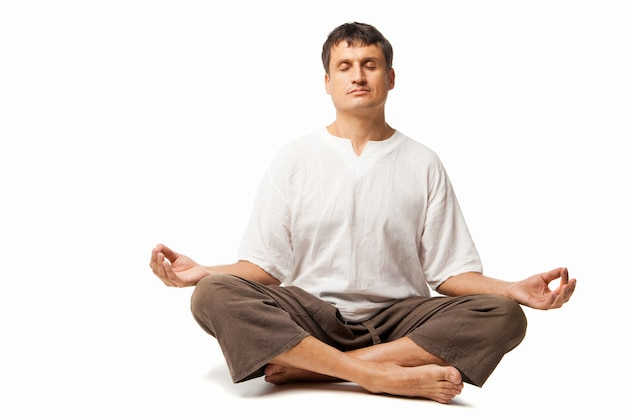 Spokojny mężczyzna uprawiający jogę i medytujący - odizolowany na białym tle